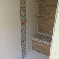 Moderne geflieste Dusche mit Sitzmöglichkeit